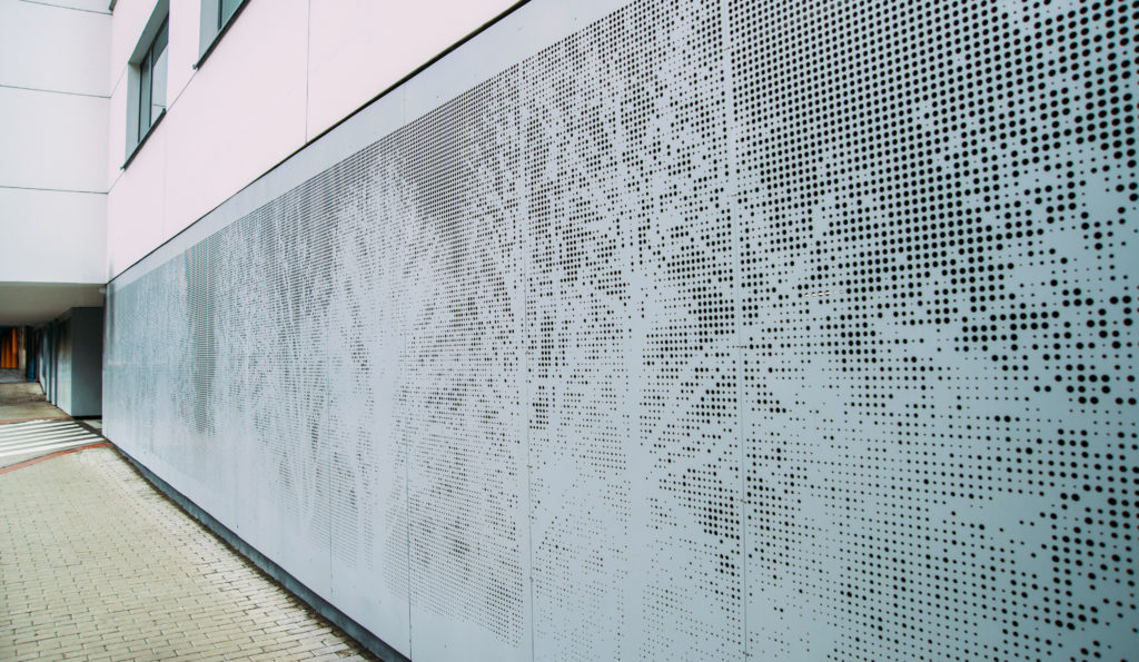 perforated grey metal panel. Trees pattern.